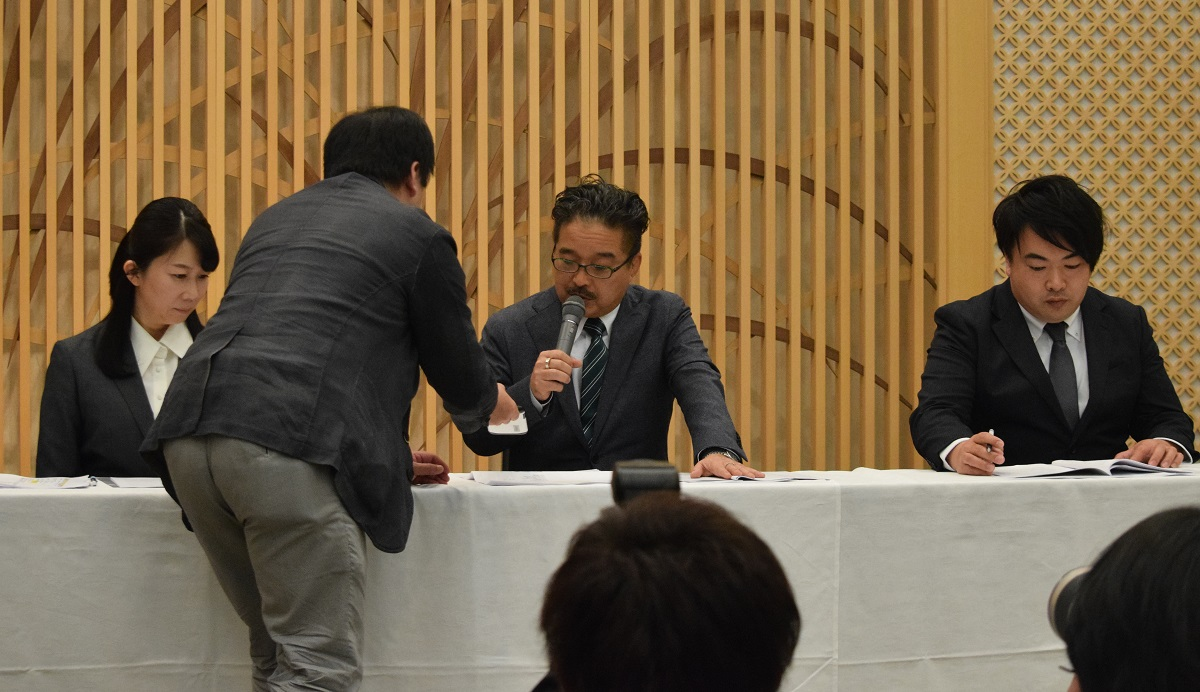 写真・図版 : 会見で松村匠・AKS取締役(中央)にツイッターの画面を見せる筆者=2019年3月22日