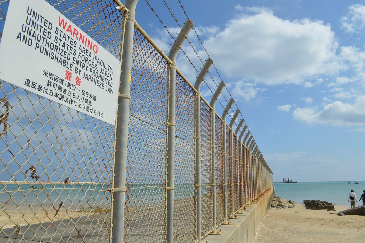 写真・図版 : 沖縄・辺野古。フェンスの向こうの米軍基地の沖で、普天間飛行場を移設するための埋め立てを日本政府がしている=2月。藤田直央撮影