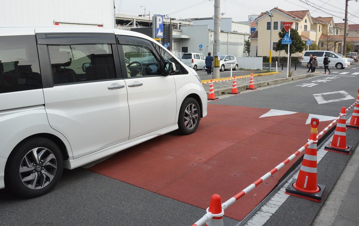 交差点の手前に設けられたハンプを通過する車。ほとんどの車が速度をゆるめていた=八幡市