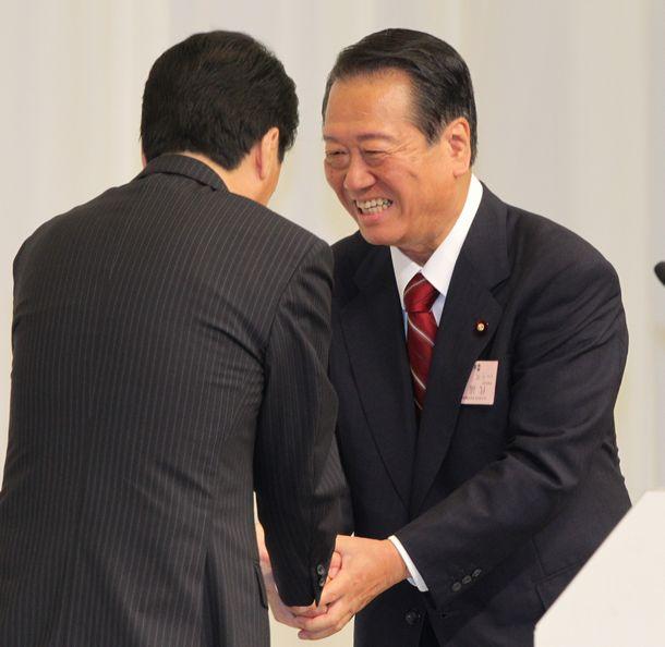 写真・図版 : 民主党代表に再選された菅直人首相(左)と握手する小沢一郎前幹事長=2010年9月14日、東京都港区