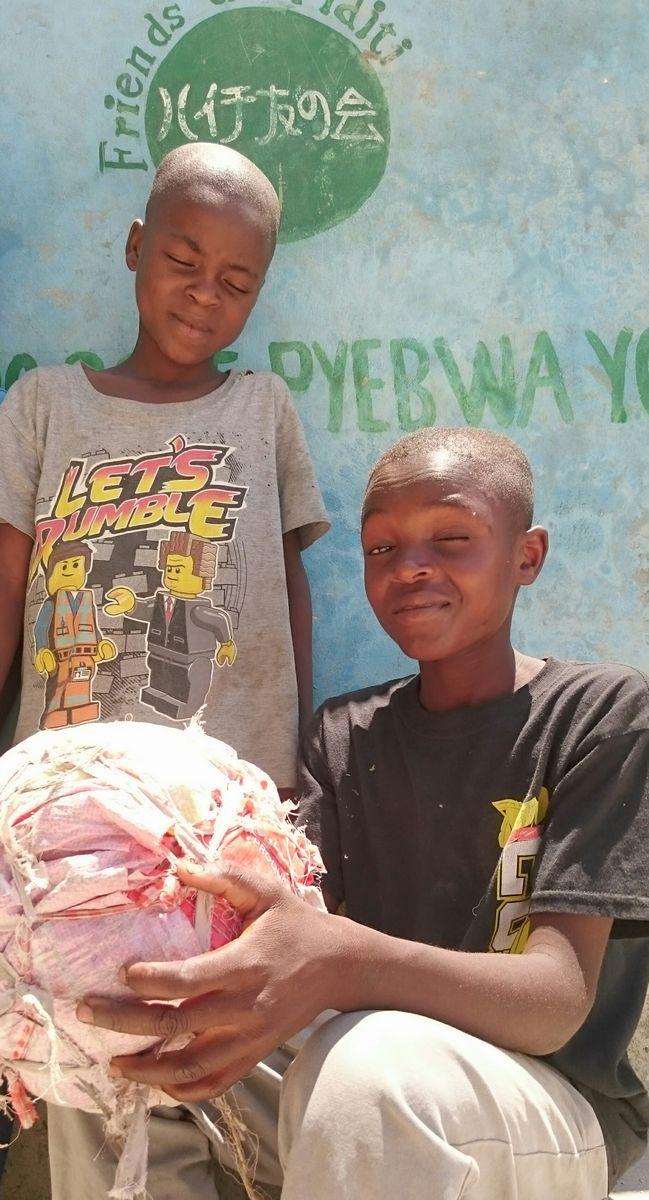 写真・図版 : 2019年4月27日、西県ガンチエ市ロッシュ村に当会の支援で設立された灌漑設備の前。少年たちは12歳。手作りのサッカーボールでゲームに興じていた=ハイチ友の会提供