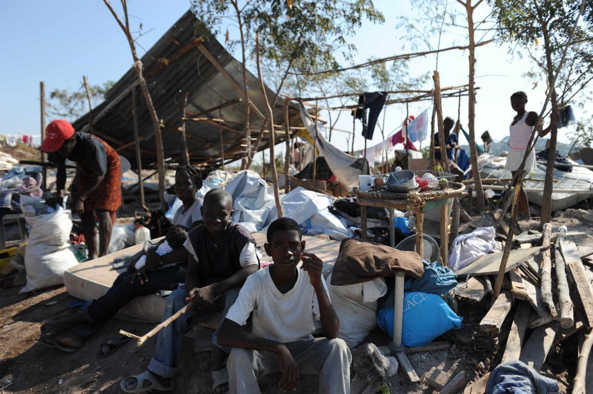 写真・図版 : ハイチ大地震の後、新しくできたスラム街で、屋根のない「家」で休む家族。この場所も警察から立ち退きを迫られていた=2010年5月18日、ハイチ・ポルトープランス