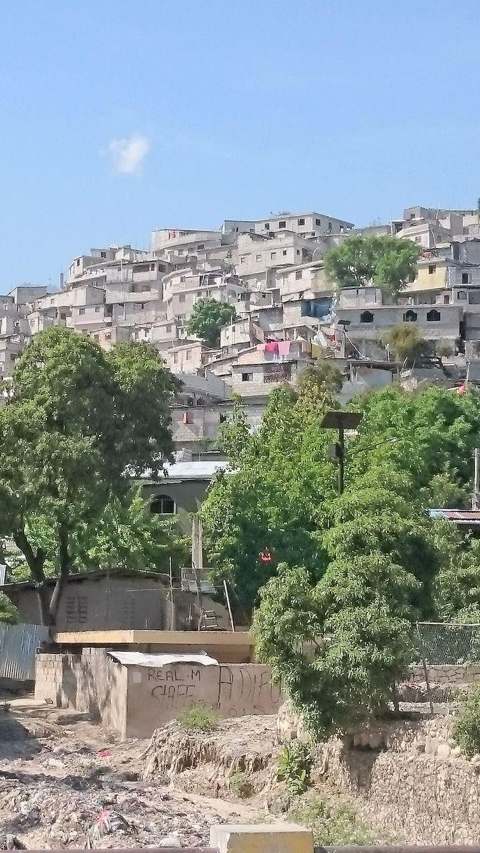 写真・図版 : 2019年4月27日、首都近郊のスラム街シテ・シクレ。ハイチ大地震で崩れたブロックの建物の上に、また脆弱なブロックの小屋を建てている=ハイチ友の会提供