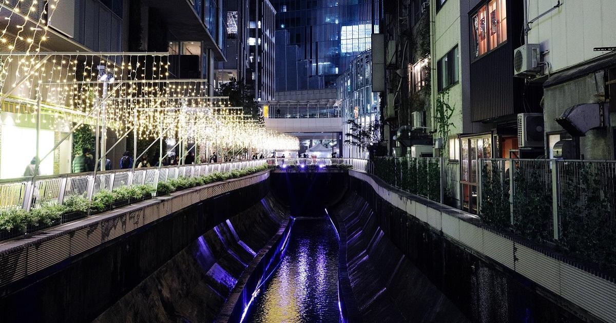 ライトアップされる渋谷川。再開発された複合施設(左)の対岸には古い建物が残る=東京都渋谷区2018年12月