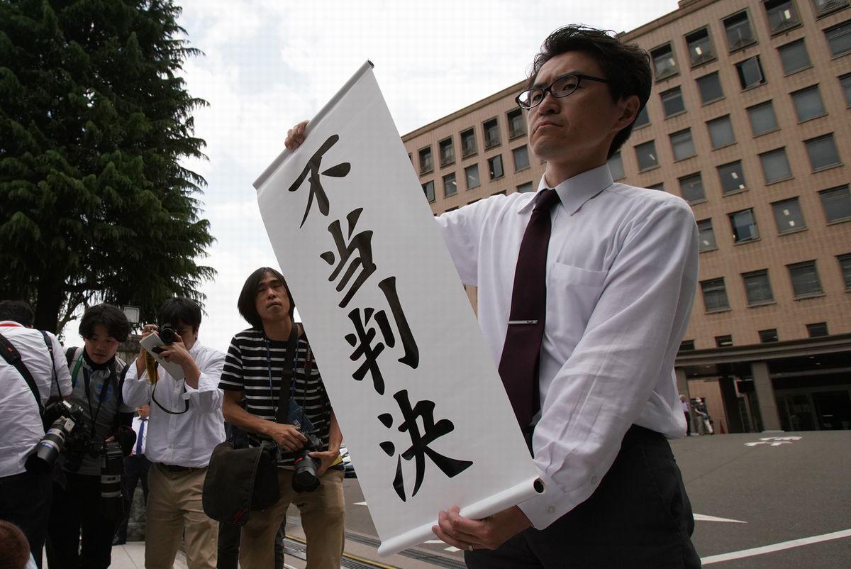 写真・図版 : 原告の請求棄却を受け「不当判決」の旗を出す弁護士=2019年5月28日午後3時3分、仙台市青葉区、小玉重隆撮影