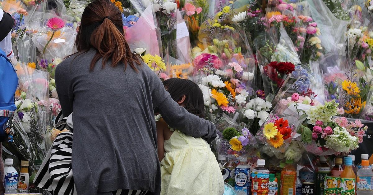 事件現場で花束を手向け、犠牲者を悼む人たち