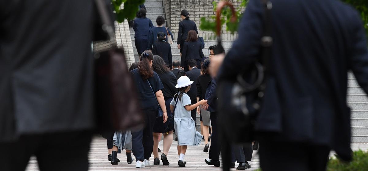 写真・図版 : 被害に遭ったカリタス学園の本部に入る保護者たち=2019年5月28日