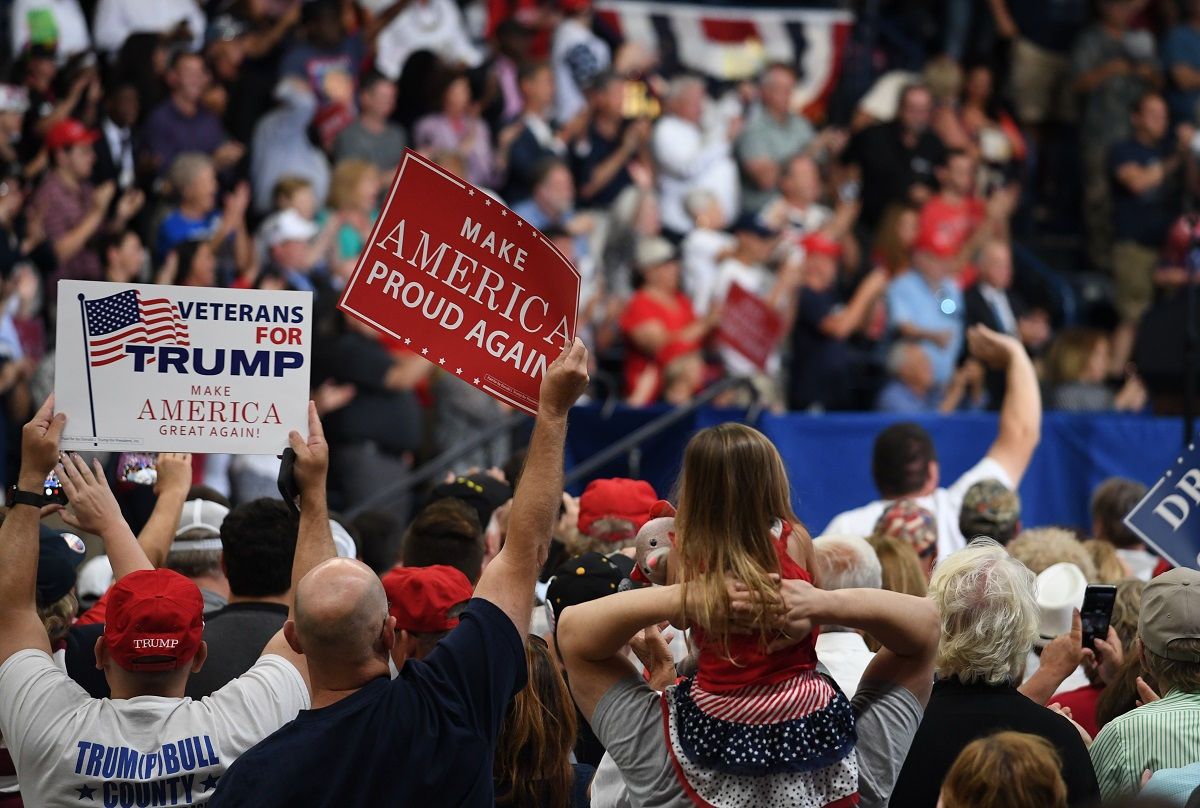 写真・図版 : トランプ米大統領の集会で「再び誇らしい米国を」とのプラカードを掲げる支持者たち=2017年7月、米オハイオ州