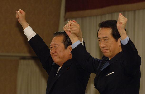 写真・図版 : 民主党代表選に勝利し、壇上で菅直人元代表と手を取り合い拍手にこたえる小沢一郎新代表=2006年4月7日、東京都内のホテル