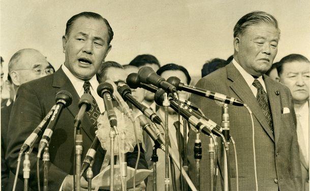 写真・図版 : ハワイでのニクソン米大統領との首脳会談を終えて帰国、声明文を読む田中角栄首相(左)。右は大平正芳外相=1972年9月3日、羽田空港