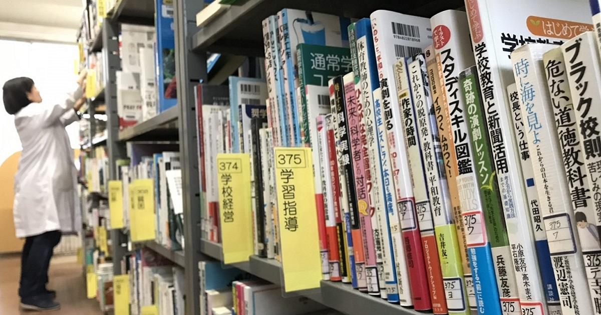 県立茅ケ崎高の図書館。背表紙のラベルは、私費で買ったことを示す青が大半で、県費で買った赤はごく一部