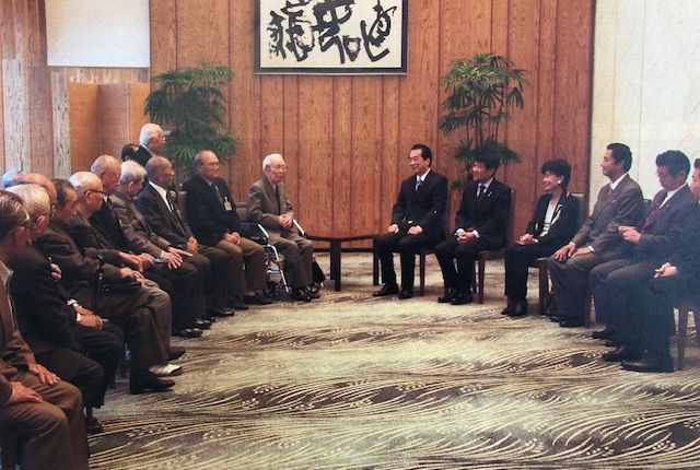写真・図版 : 首相官邸へ法案成立のお礼に出かけた抑留帰国者の人々。中央は菅直人総理。その右が谷博之さん、円、那谷屋正義さん=2010年7月頃(筆者提供)