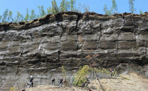 写真・図版 : 永久凍土が崩落してできたバタガイカ・クレーター。下の方に、壁面を見上げる人たちがいる=「マンモス展」PR事務局提供