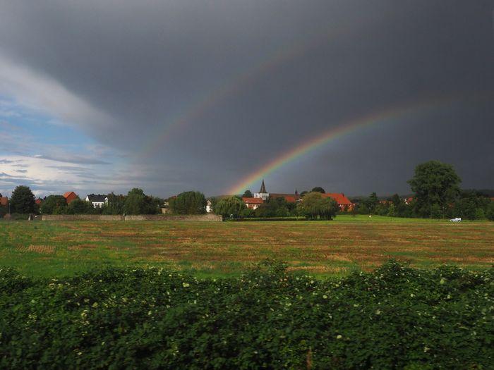 写真・図版 : 車窓からの風景。小雨交じりの風景の向こうに、二重の虹がかかった