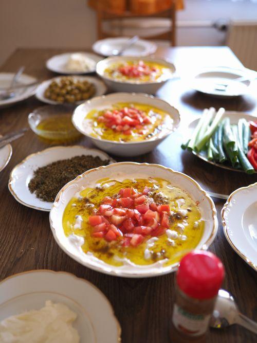 写真・図版 : アリさん宅の朝ごはん。ひよこ豆のペーストや、新鮮な野菜が並ぶ