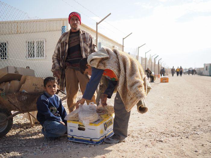 写真・図版 : 配られたばかりのパンを、キャンプの片隅で売る父子