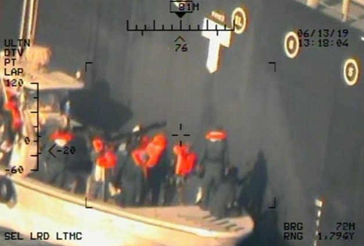 写真・図版 : 米国防総省が公開した写真。米側は、日本の海運会社が運航するタンカーからイランの革命防衛隊が不発の水雷を除去する様子だと主張している