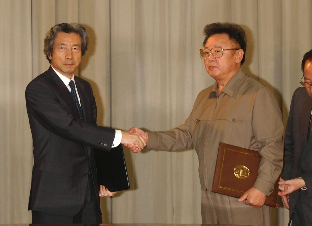 写真・図版 : 2002年9月、初の日朝首脳会談後に互いに署名した日朝平壌宣言を交換し、握手する小泉純一郎首相と金正日総書記=平壌の百花園迎賓館。代表撮影