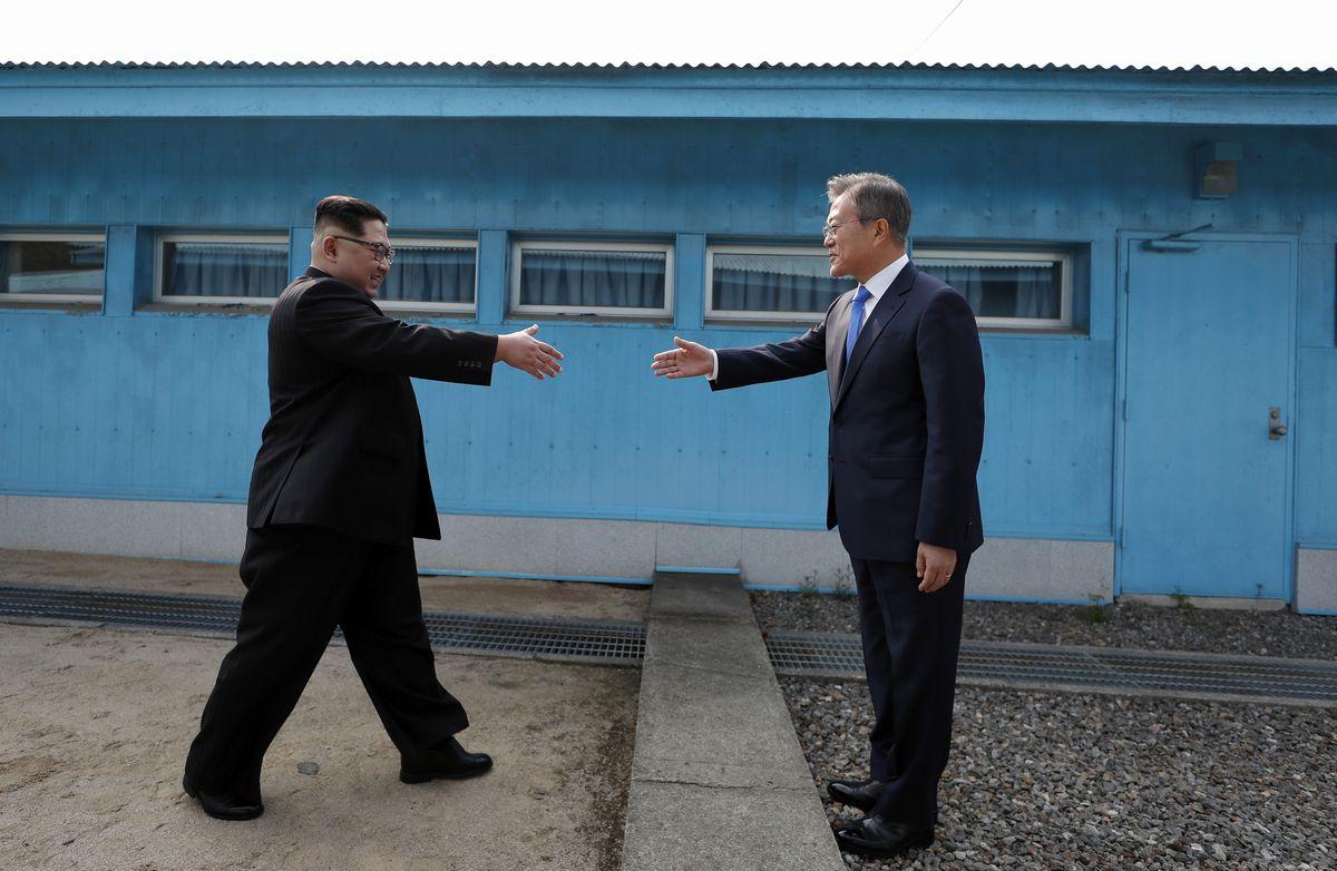写真・図版 : 2018年4月、南北首脳会談を前に板門店で軍事境界線を挟んで握手しようとする北朝鮮の金正恩委員長(右)と韓国の文在寅大統領=韓国共同写真記者団撮影