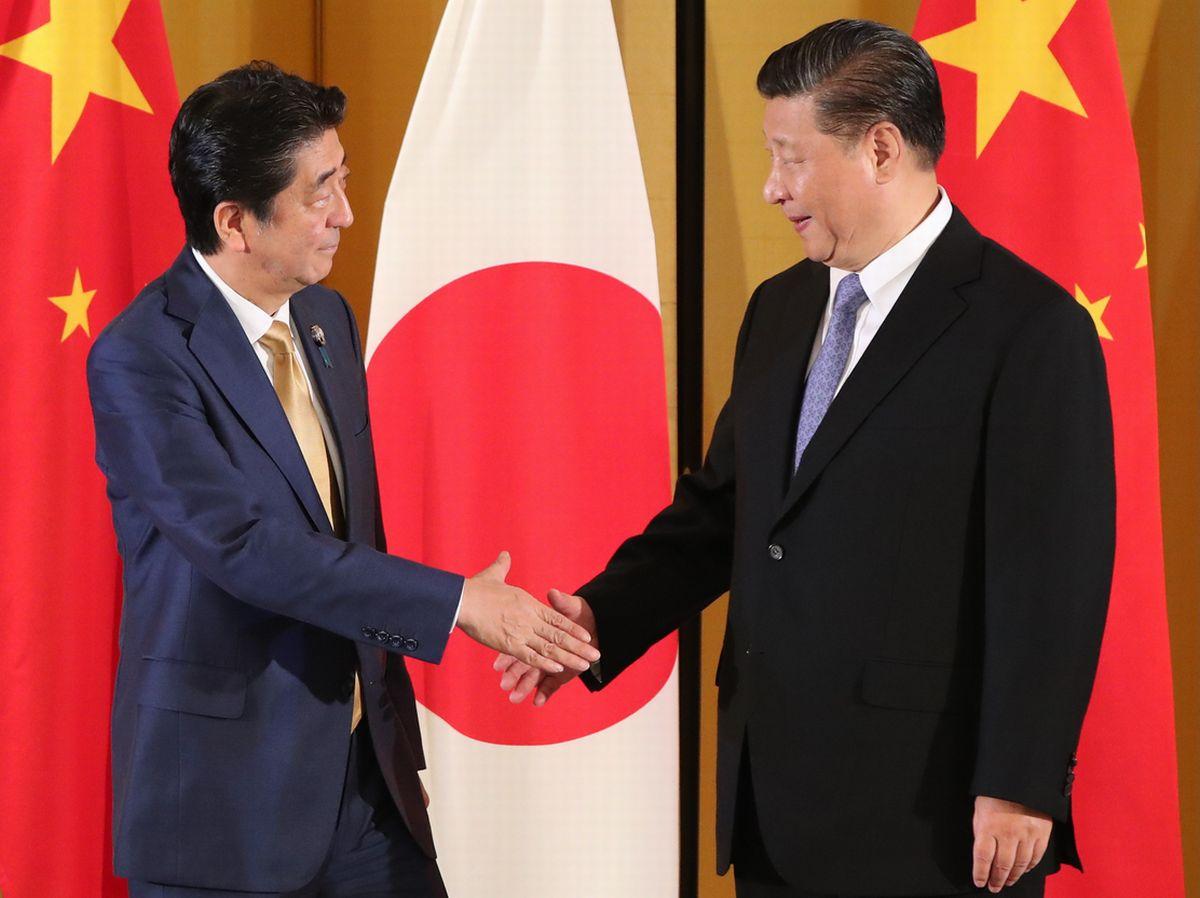 写真・図版 : G20サミットで来日した習国家主席と、日中首脳会談を前に握手する安倍首相=6月27日夜、大阪市北区。代表撮影