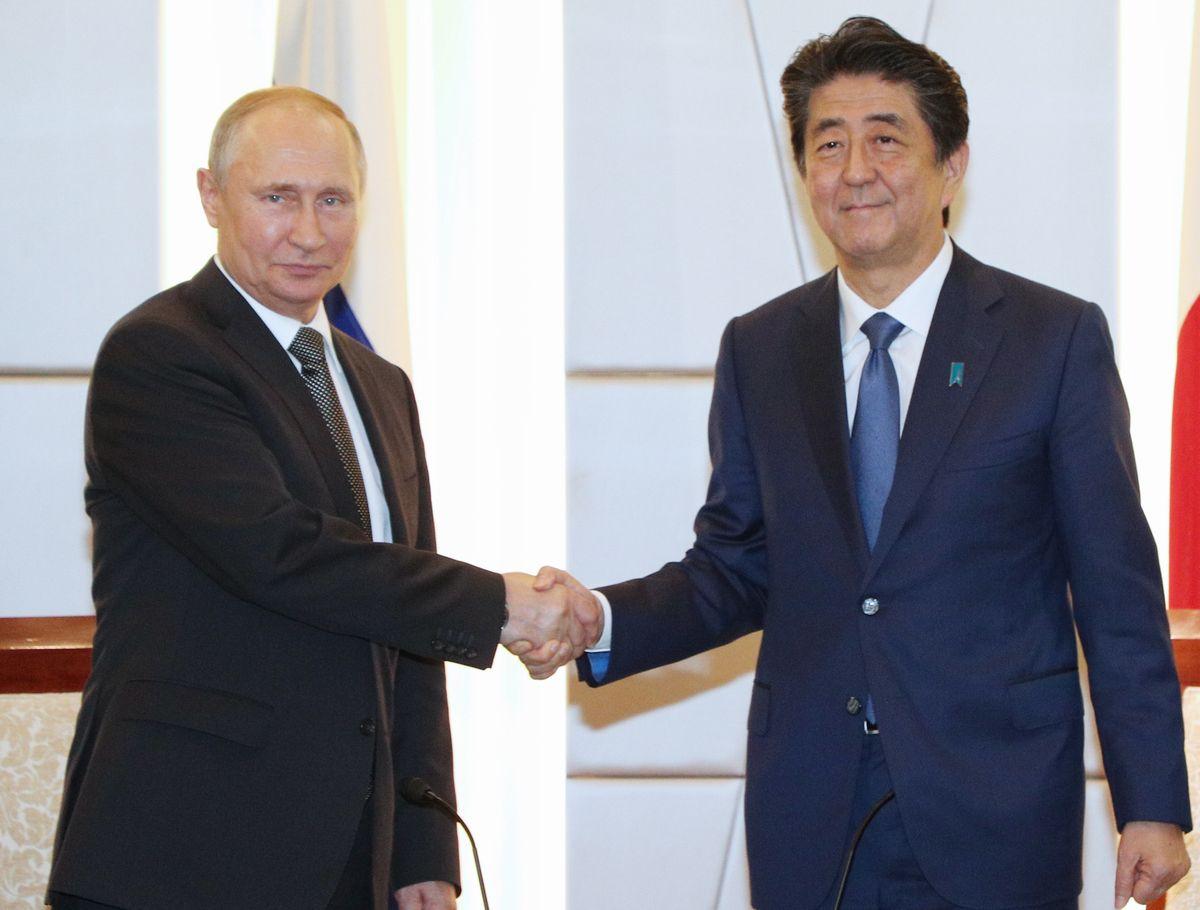 写真・図版 : G20サミットで来日したプーチン大統領と、日ロ首脳会談を前に握手する安倍首相=6月29日夕、大阪市中央区。代表撮影