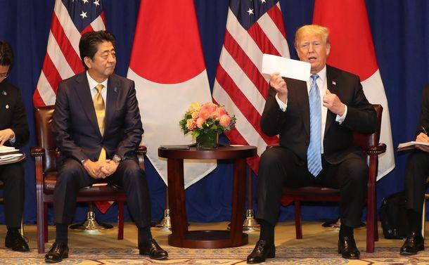 写真・図版 : 2018年9月の日米首脳会談で書類を見せるトランプ大統領と、安倍晋三首相=米ニューヨークのホテル。朝日新聞社