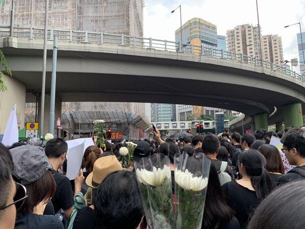 写真・図版 : 黒い服をまとい花を手に参加する人々(撮影:五野井郁夫)