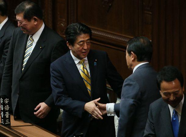 写真・図版 : 衆院解散後、麻生太郎財務相と握手する安倍晋三首相=2014年11月21日