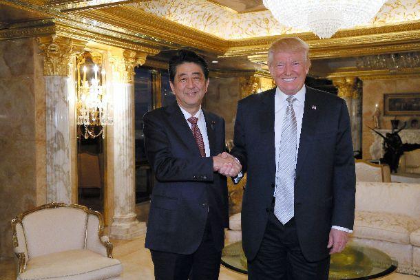 写真・図版 : トランプ次期米大統領(右)と会談し、握手する安倍晋三首相=2016年11月18日、ニューヨーク、内閣広報室提供