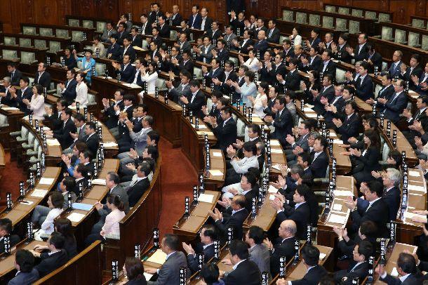 写真・図版 : 参院本会議で安保関連法が可決・成立し、拍手する与党議員(中央付近)=2015年9月19日