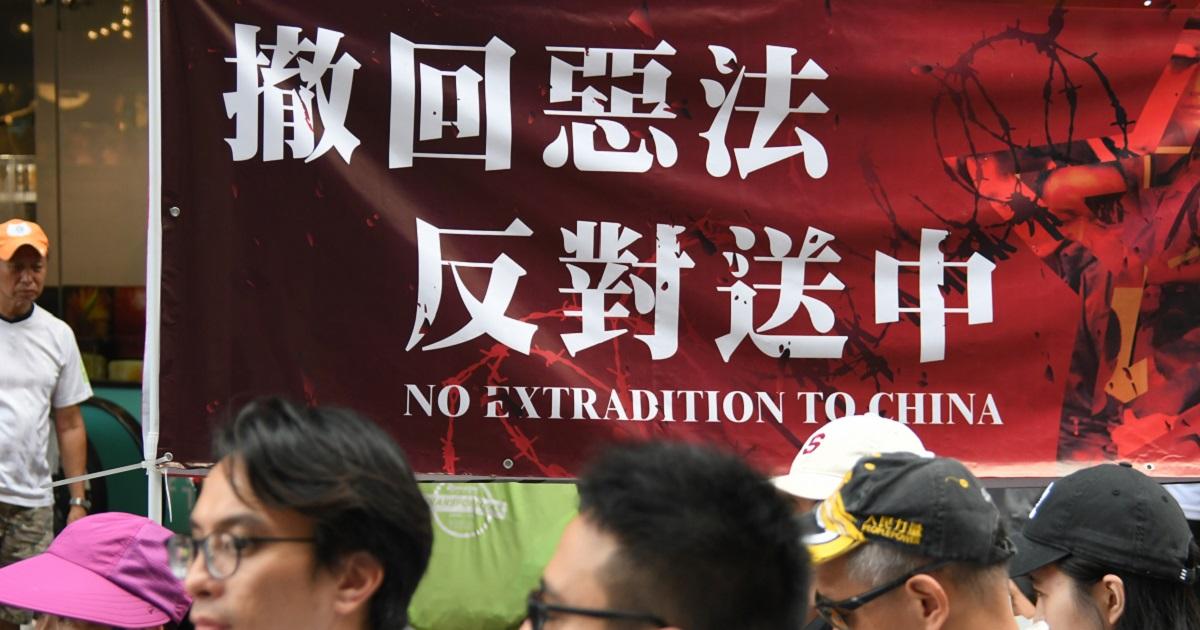 写真・図版 : 「逃亡犯条例」改正に反対し、「悪法を撤回せよ」「中国への引き渡しに反対」と書かれた横断幕を掲げた香港市民のデモ=2019年6月9日