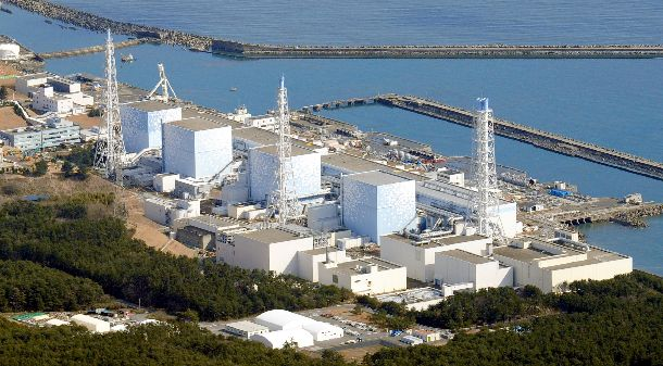 写真・図版 : 津波被害を受けた後の東京電力福島第一原子力発電所1号機(左)から4号機。爆発事故はまだ起きていない=2011年3月12日午前9時28分、福島県大熊町