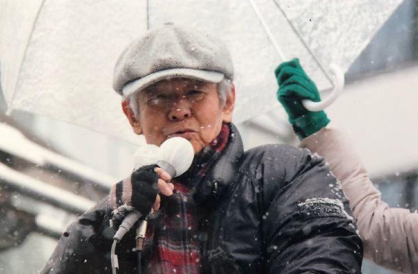 写真・図版 : 都知事選の選挙戦最終日。降りしきる雪のなか、数奇屋橋で細川さんの応援演説をする菅原文太さん。傘をさしかけているのは円=2014年2月8日