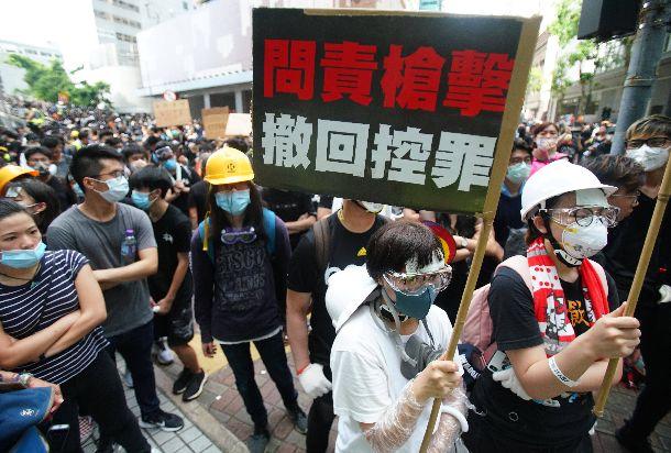 写真・図版 : 香港警察本部前でメッセージを手に抗議するデモ参加者=2019年6月21日、香港