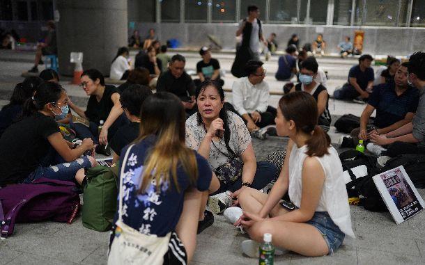 写真・図版 : 立法会(議会)前に座り込むデモ参加者。政治について話したり、メッセージを書いたりと静かな抗議が続いていた=2019年6月19日、香港