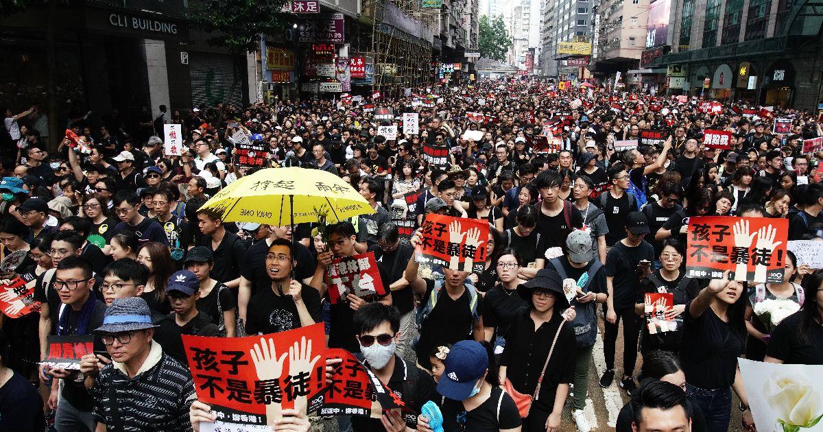 写真・図版 : メッセージが書かれた紙を手にデモに参加する人たち=2019年6月16日、香港