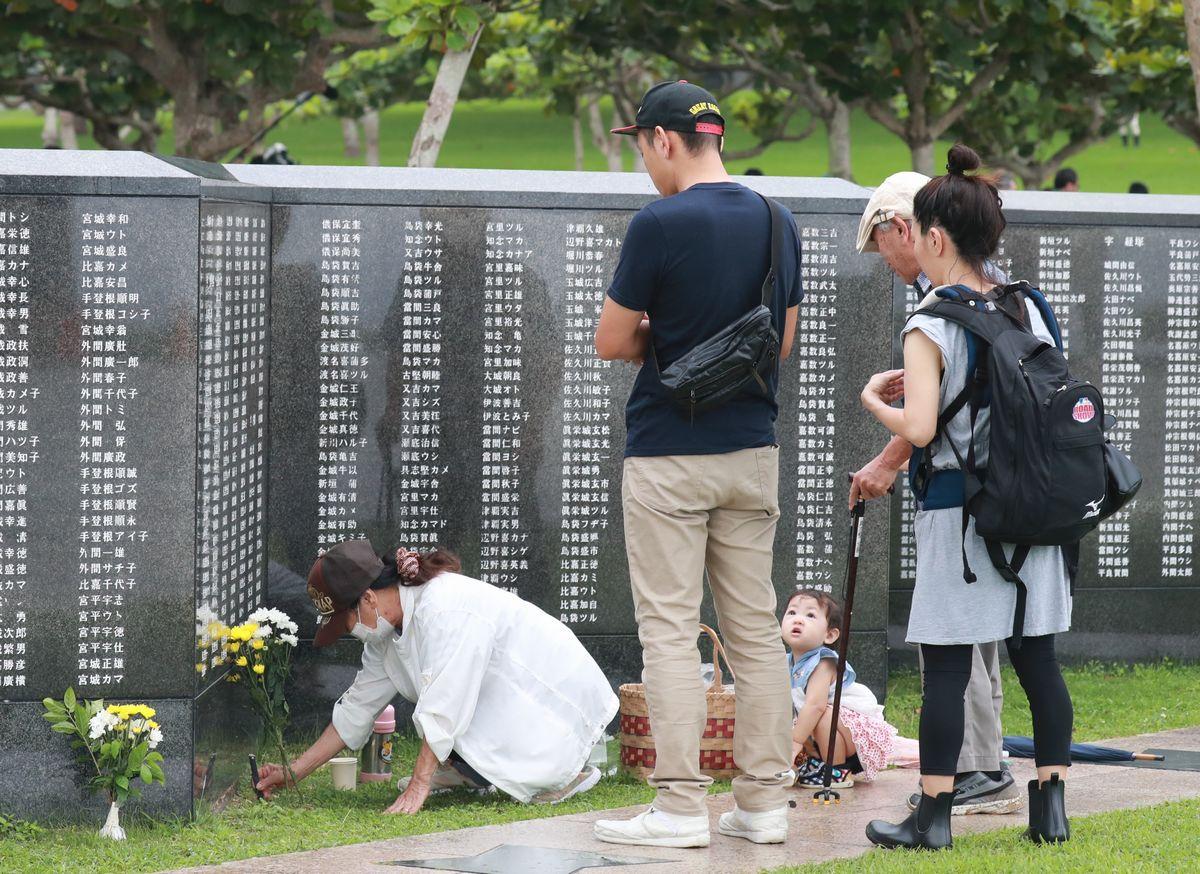 写真・図版 : 平和の礎を訪れ、戦没した親類を供養する家族=2019年6月23日午前7時50分ごろ、糸満市摩文仁の平和祈念公園(琉球新報提供)
