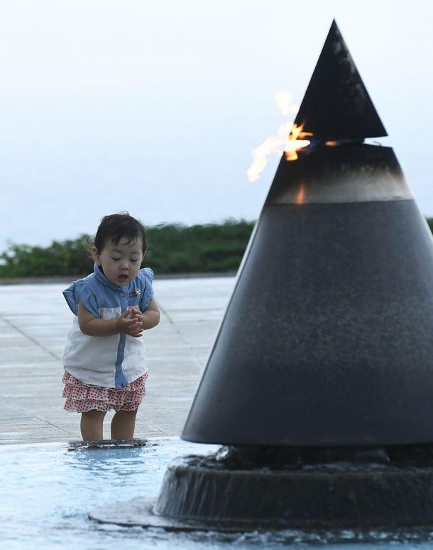 写真・図版 : 平和の礎の「平和の火」に手を合わせる幼児=2019年6月23日午前7時54分、糸満市摩文仁の平和祈念公園(琉球新報提供)