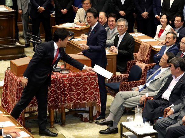写真・図版 : 党首討論で、安倍晋三首相(中央)から返された金融庁の審議会報告書を、麻生太郎財務相兼金融相(前列右から2人目)に渡そうとする国民民主党の玉木雄一郎代表(左)=2019年6月19日