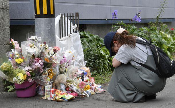 写真・図版 : 池田詩梨ちゃんが住んでいたマンション前には花や菓子が置かれている。女性が訪れ、涙を流していた=6月12日、札幌市中央区