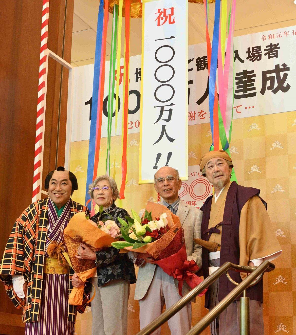 博多座の1千万人目の入場者となった夫妻を祝う武田鉄矢さん(右)とコロッケさん(左)=10日、福岡市博多区 201905010日