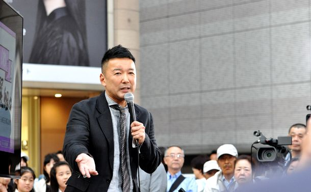 写真・図版 : 街頭で訴える山本太郎氏。演説は聴衆の質問に答える形で進む=2019年5月29日、東京・北千住駅