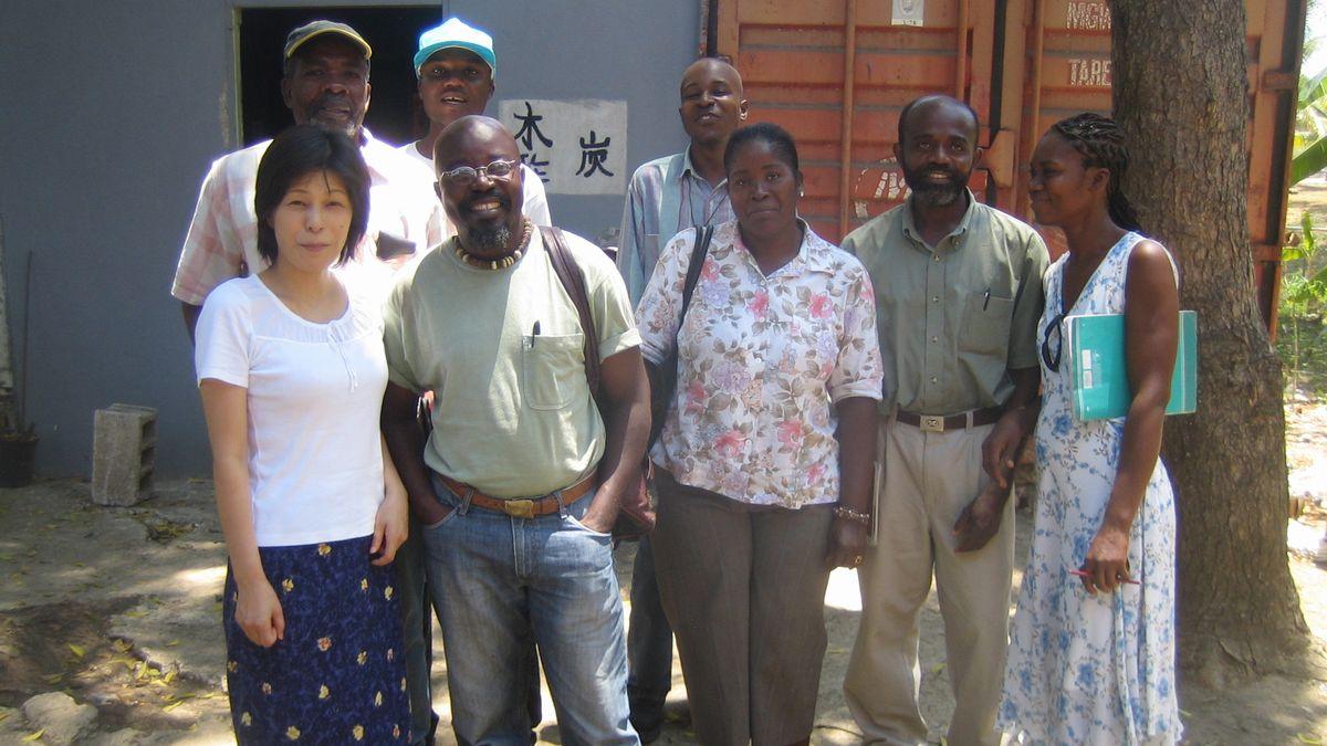 写真・図版 : 2006年、レオガン市近郊の修道会の敷地内に間借りしたGEDDHのオフィス前でスタッフと撮影。炭・木酢と漢字で書かれている=小澤幸子さん提供