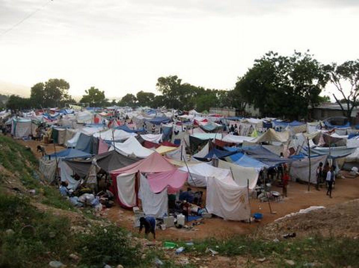 写真・図版 : 2010年4月、大地震後にできたテント村=小澤幸子さん提供