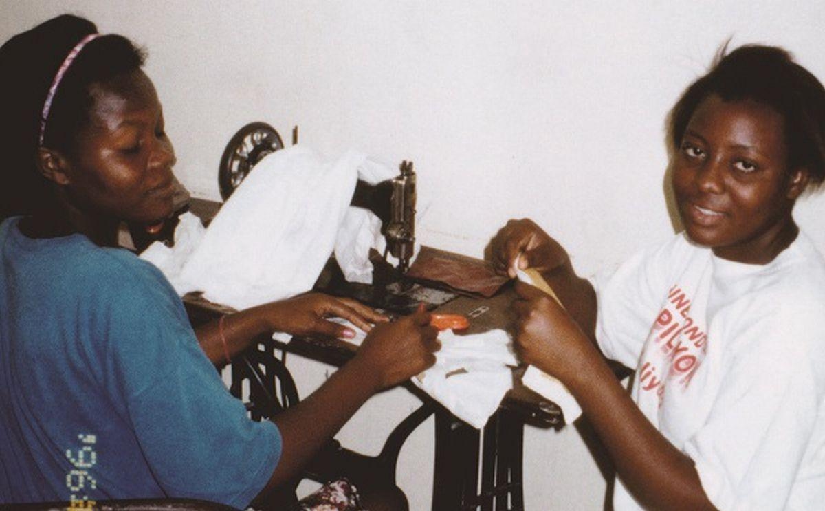 写真・図版 : 1996年、首都ポルトープランスの職業訓練校。女性たちに収入があれば、子どもたちにも恩恵があると考えて、絵はがき販売の収益約120万円で中古のインド製足踏みミシン204台を購入して寄贈した=小澤幸子さん提供