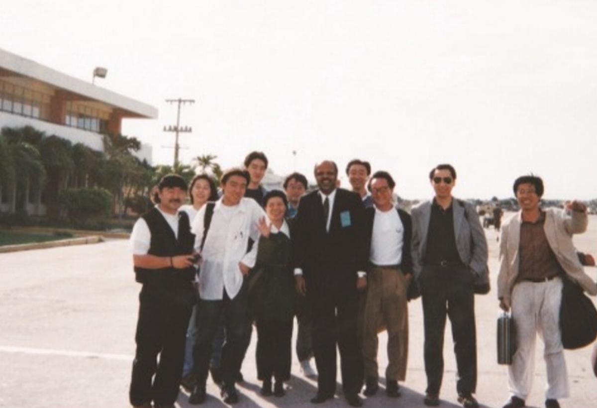 写真・図版 : 1994年11月、ハイチ国際空港に初めて降り立った小澤幸子さん(左から2番目)。この後、到着ロビーでバックパックを奪われる=小澤さん提供
