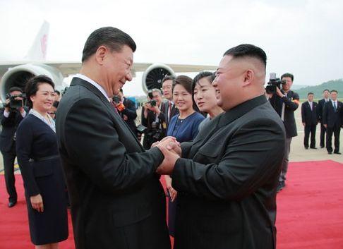 写真・図版 : 平壌空港で金正恩・朝鮮労働党委員長(右)の出迎えを受ける中国の習近平国家主席=2019年6月20日、労働新聞ホームページから