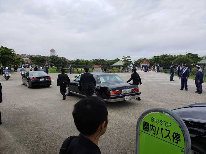 写真・図版 : 追悼式の後、会場をあとにする安倍首相の車を走りながら護衛するSPたち