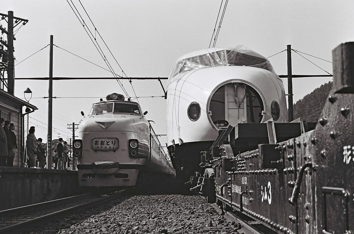 写真・図版 : 1964年、鴨宮へ輸送される東海道新幹線の0系量産先行車。左は特急「おおとり」。狭軌の特急電車とくらべると標準軌の新幹線の車体幅の広さがわかる