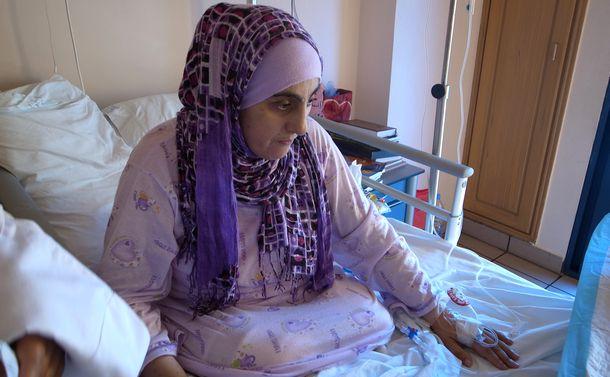 写真・図版 : シリア政府軍の砲撃で両足を失い、レバノンに密出国して病院に入院していたシリア人女性=2012年6月14日、レバノン北部トリポリ(筆者撮影)